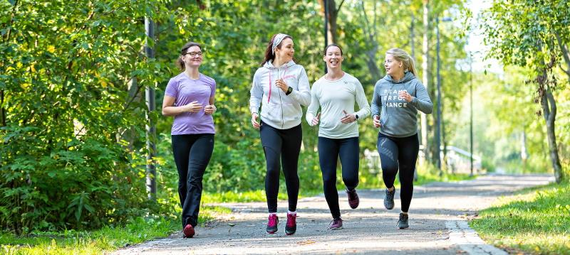 Naiset juoksevat kesäisessä puistossa